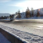 A car loses snow from its roof as it drives over the dip on I-90 near Kellogg.