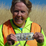 Gretchen Sherlin holds a $100 bill, found while collecting litter along ID-20