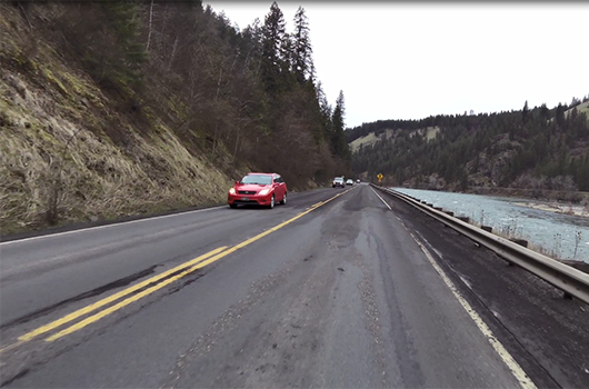 Car drives on deteriorating pavement on US-12 between Big Canyon (Peck) and Orofino