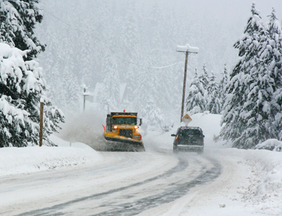 Winter weather scene with a snow plow clearing the road
