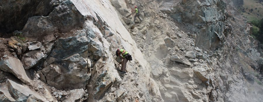 Rock scalers dislodge loose material on the slope above US-95 at milepost 188