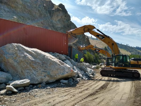Operators weigh down protective containers near the temporary road around the US-95 MP 188 slide