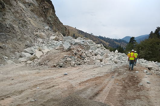 Workers walk through the shoofly on US-95 at milepost 188 after the biggest boulders were blasted