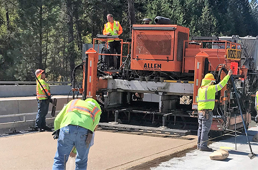 Photo of contractors redoing the driving surface on the westbound bridge over Blue Creek Bay