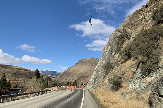 A helicopter helps install cable netting on the US-95 slide south of Riggins