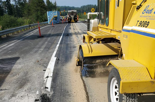 A broomer follows a truck putting down sand
