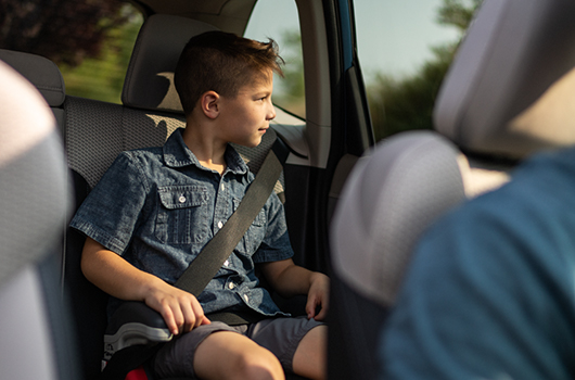 Young boy sitting buckled up in booster seat in the back of a car.